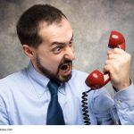 verärgerter Geschäftsmann, der in sein Telefon schreit